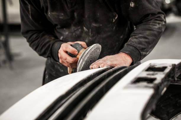 Karosseriereparaturtechniker entfernt überschüssige Befüllung aus einer unfallgeschädigten Autostoßstange mit einem pneumatischen Schleifer – Foto