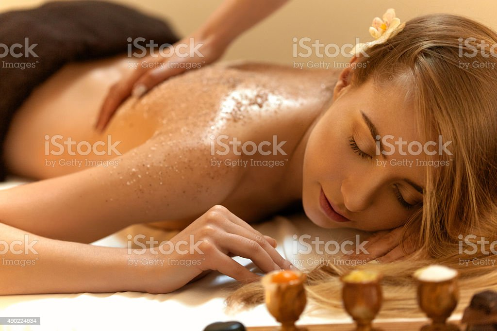 Body Scrub. Beautiful Blonde Gets a Salt Scrub Beauty Treatment stock photo