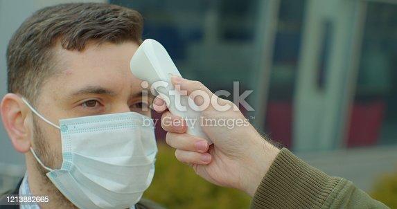 COVID-19 Body temperature measuring for coronavirus. A man's temperature is taken for controlling disease