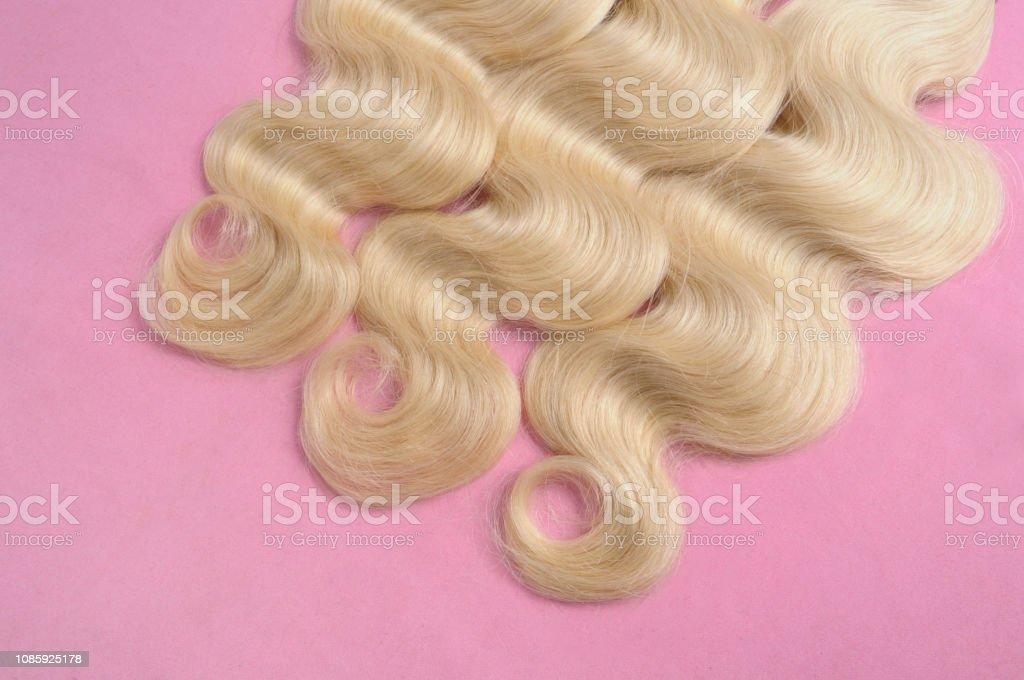 blonde wavy hair on pink background