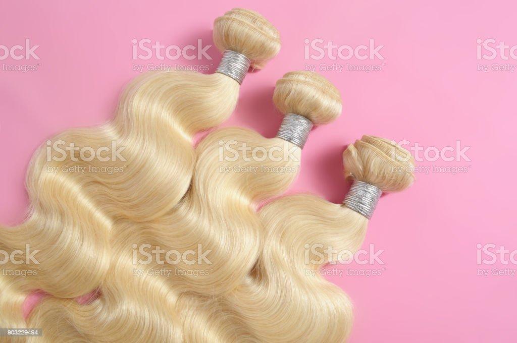 blonde human hair bundles on pink bacground