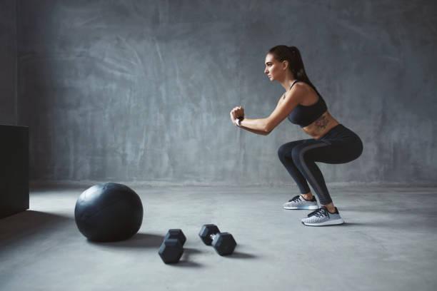 entrenamiento del cuerpo. fitness mujer en ropa deportiva con estilo ejercicio - agacharse fotografías e imágenes de stock