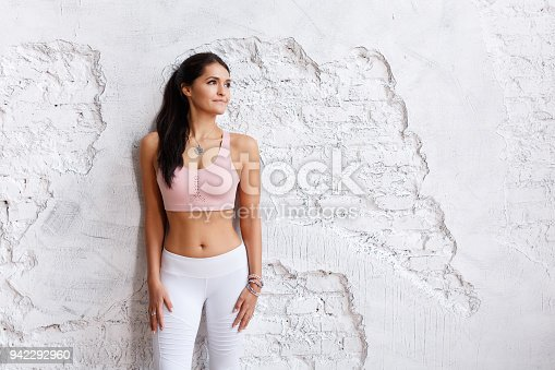 istock Bodybilduing and sport concept. Young fit pretty woman dressed in sport clothes, going to have fitness course with trainer, poses against white brick wall 942292960