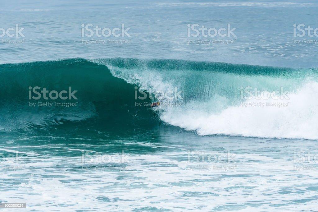 Bodyboarder surfing ocean wave stock photo