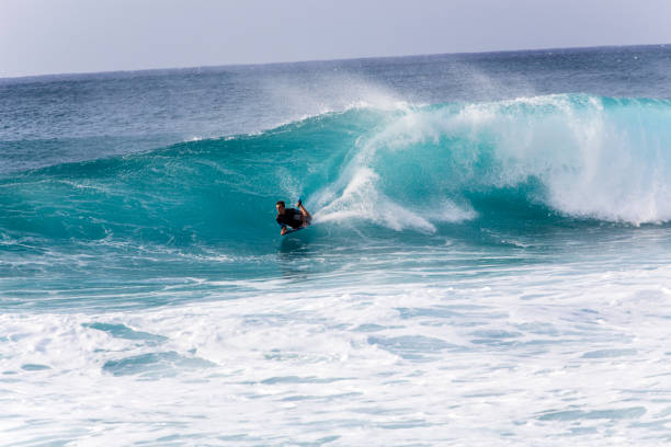 Bodyboarding the raging waves of Banzai Pipeline stock photo