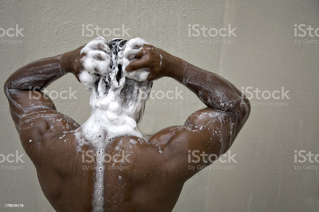 bodybuilder back with soap in the shower stock photo