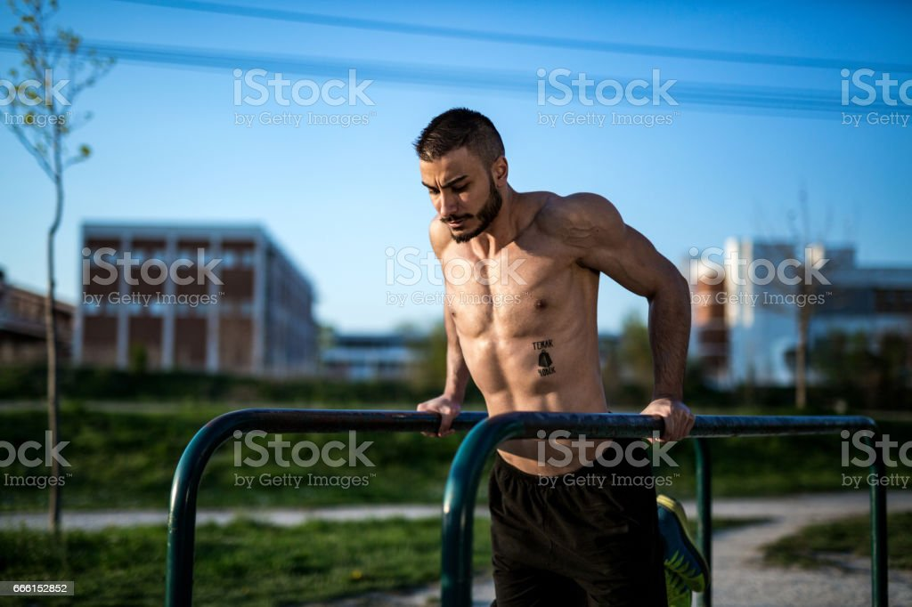 Bodybuilder doing dips in a public gym stock photo