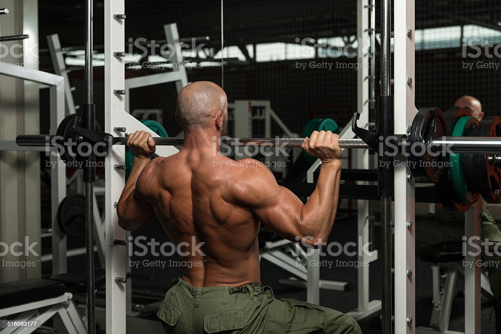 Bodybuilder Doing Heavy Weight Exercise For Shoulder stock photo