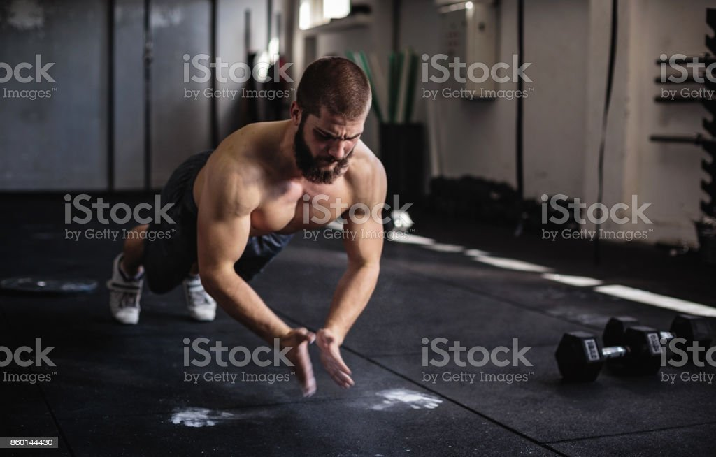 Bodybuilder doing push-ups in the gym stock photo