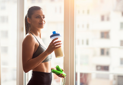 Bodybuilder girl relax after exhausting training, Young athlete drinking sports drink after workout, beautiful woman resting after exercising training, young sports model holding protein shaker and skipping rope around the window.