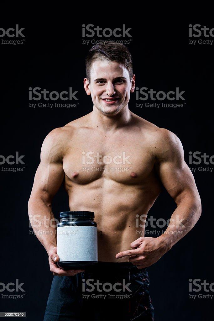 Bodybuilder holding a black plastic jar blank white label whey stock photo