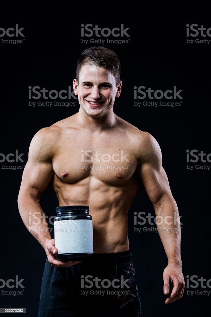 Bodybuilder holding a black plastic jar blank white label with stock photo