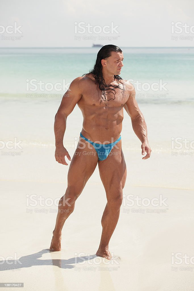 Bodybuilder on the beach stock photo
