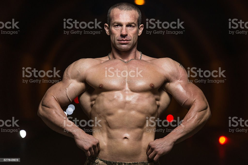 Bodybuilder Performing Front Lat Spread Poses In Tunnel stock photo