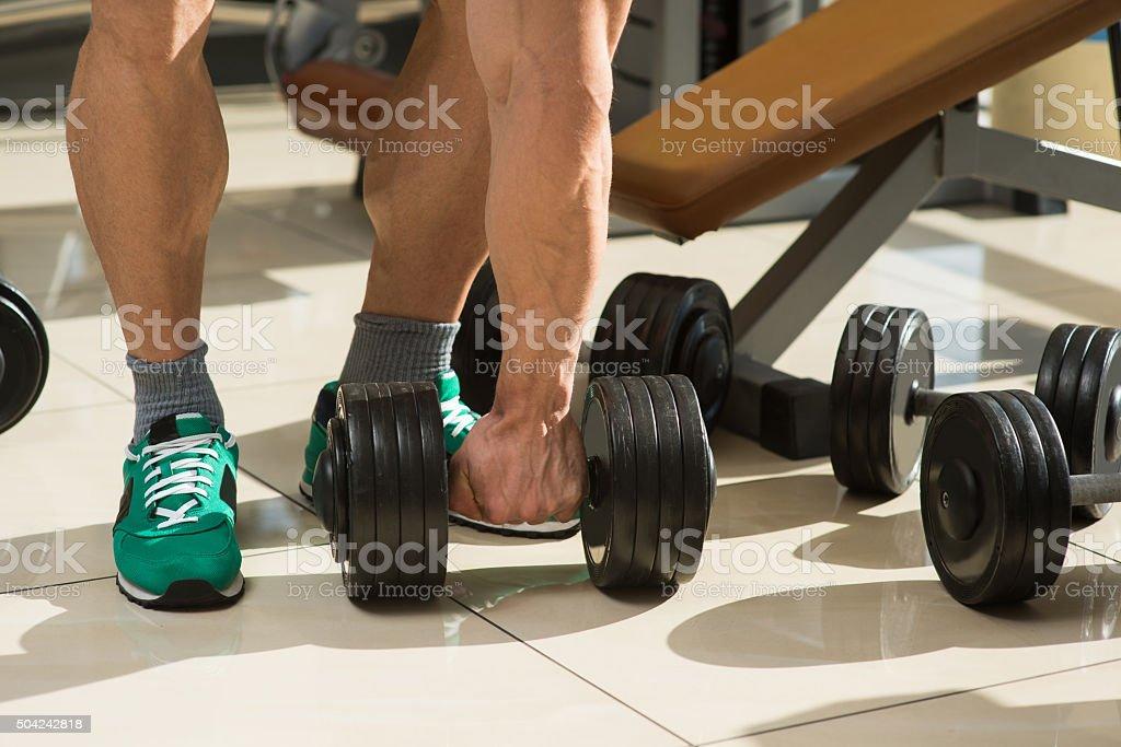 Bodybuilder picks up dumbbells. stock photo