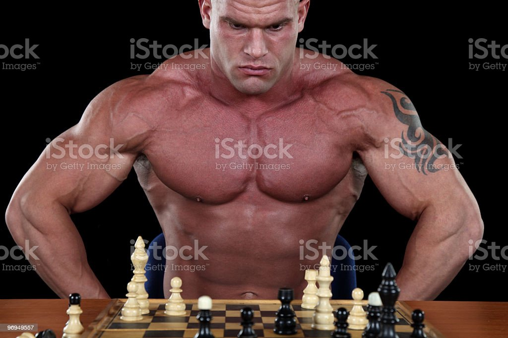 Bodybuilder playing Chess royalty-free stock photo