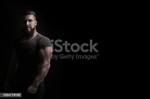 Bodybuilder portrait. Muscular man in a tight t-shirt. Dramatic portrait in unsaturated colors.