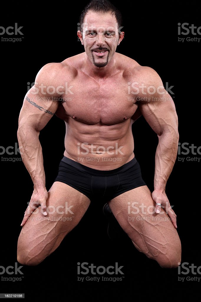 Bodybuilder posing against black background royalty-free stock photo