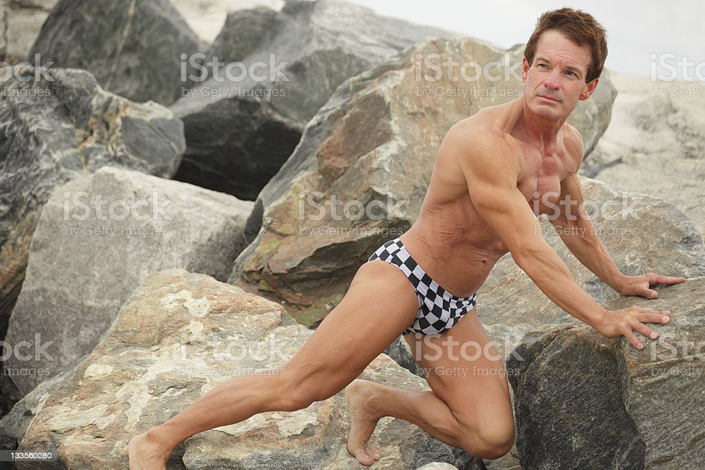 Bodybuilder posing on the rocks stock photo