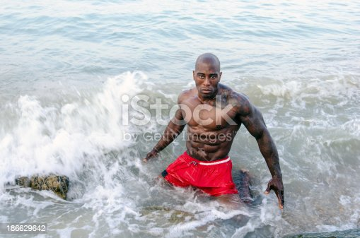 519676858istockphoto Bodybuilder relaxing om the beach after working out 186629642