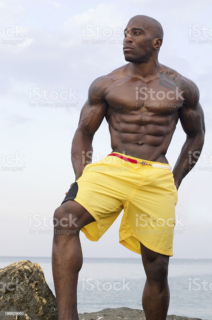 Bodybuilder relaxing om the beach after working out stock photo