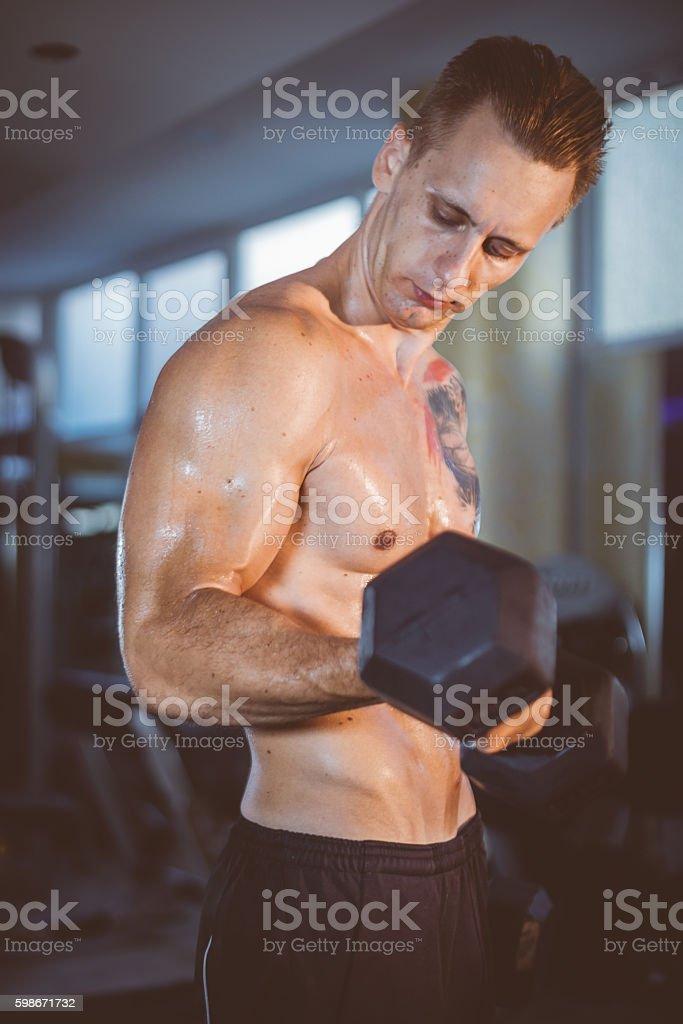 Bodybuilder shaping his biceps stock photo