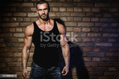 Handsome bodybuilder wearing black tank top with empty space for your text or logo