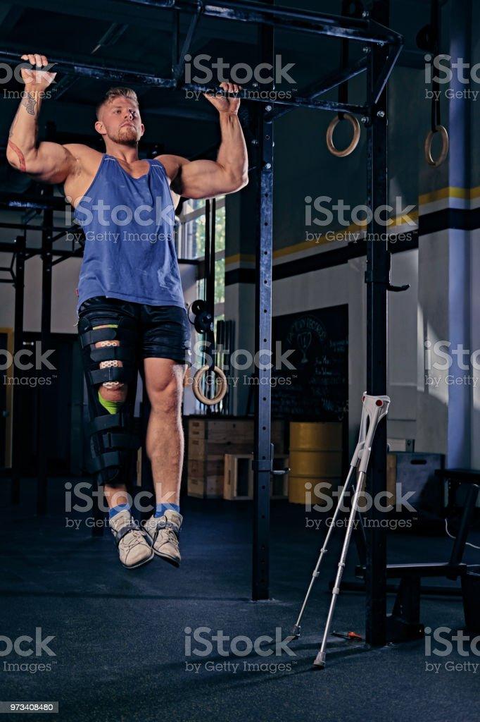 Bodybuilder with injured leg doing pull ups. stock photo