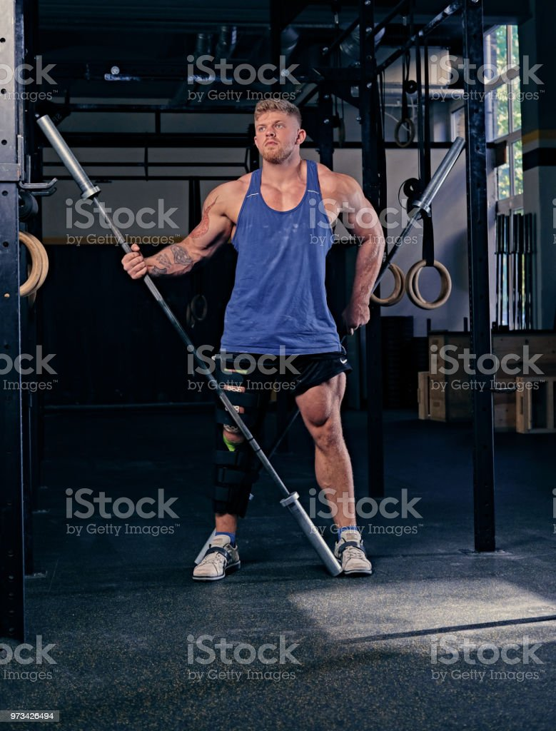 Bodybuilder with injured leg holds barbell. stock photo