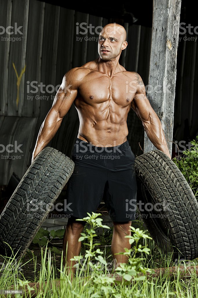 Bodybuilder with tires royalty-free stock photo