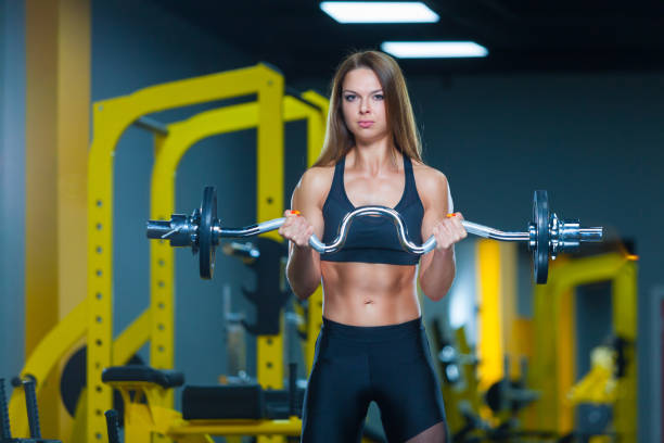 Bodybuilder woman lifting curl bar barbell in modern gym. Front view. Muscles woman showing sixpack abs stock photo