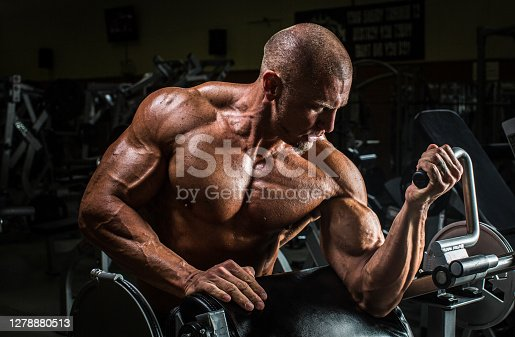 A middle aged ripped bodybuilder working out at a gym.