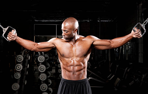 Bodybuilder working out in gym stock photo