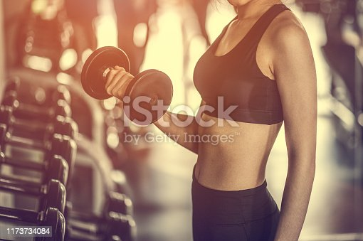 istock Bodybuilder working out with dumbbell weights at the gym. 1173734084