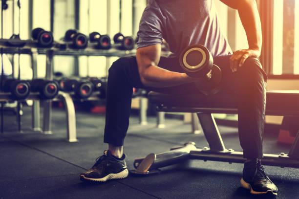 culturista haciendo ejercicio con pesas de mancuerna en el gym.man culturista haciendo ejercicios con mancuerna. cuerpo musculoso de fitness - bíceps fotografías e imágenes de stock