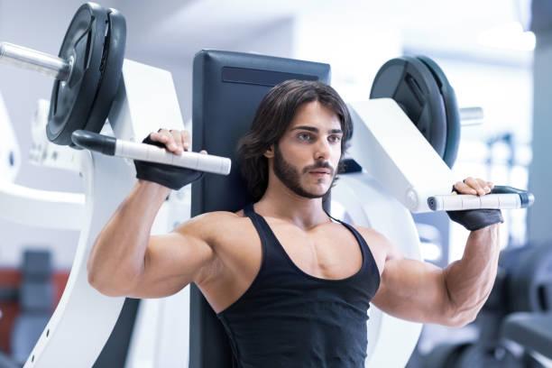 Bodybuilder trainieren mit Schulter-Presse-Maschine – Foto