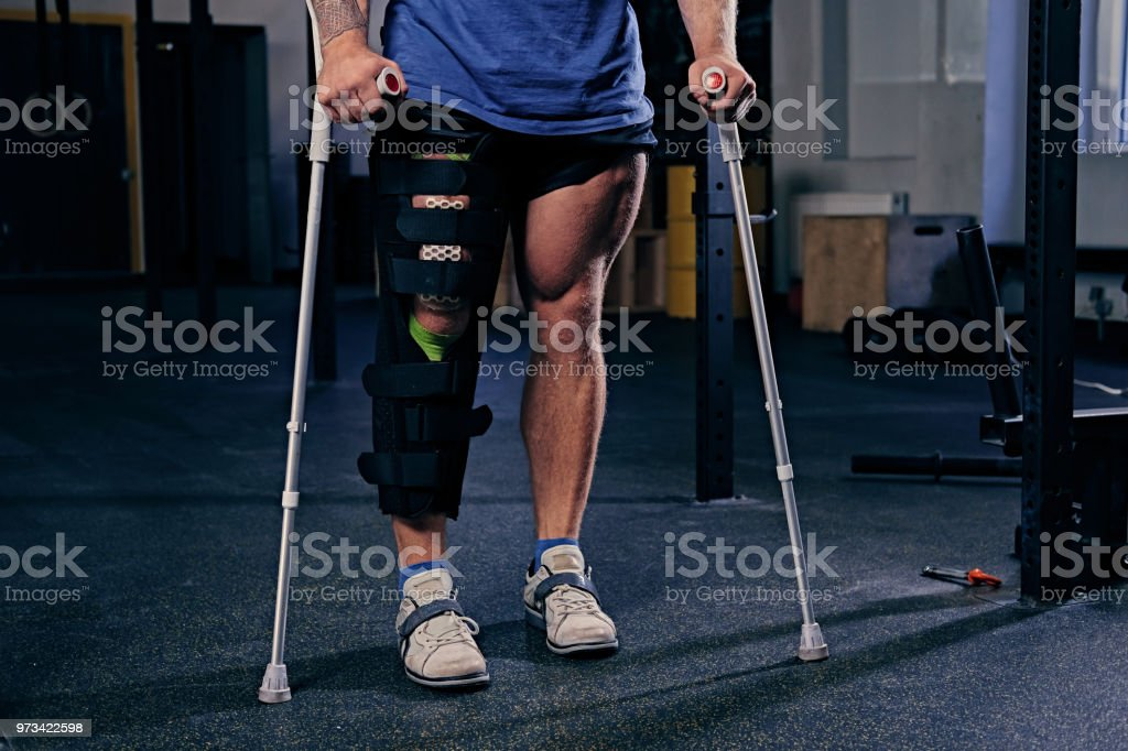 Bodybuilder's leg in bandage with crutches. stock photo