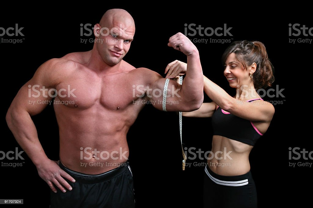 Bodybuilding couple with tape measure royalty-free stock photo