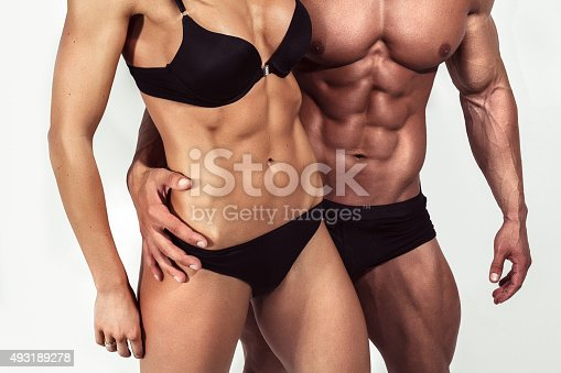 istock Bodybuilding. Strong man and a woman posing on white background 493189278