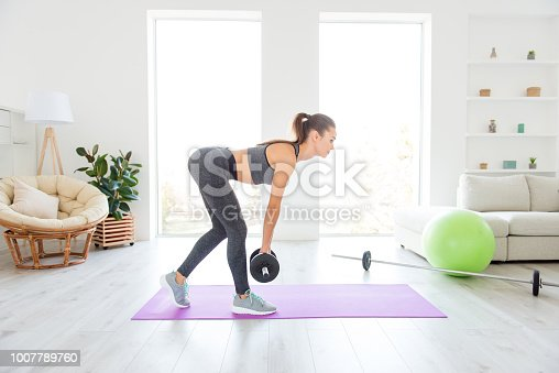 istock Bodycare beauty athletic weight holding in hands concept. Profile view photo portrait of beautiful sexy sexual focused confident lady using heavy dumbbells for making her body attractive 1007789760