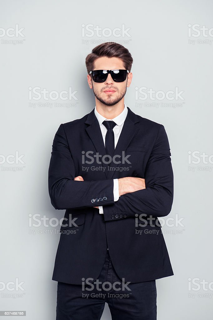 bodyguard in black suit and glasses with crossed hans - foto de stock