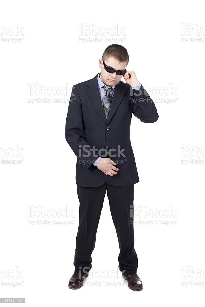 Bodyguard in suit and sunglasses against a white background stock photo