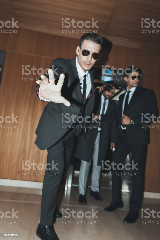 Bodyguard in sunglasses stopping paparazzi when celebrity going out from  elevator - Stock image .