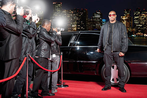 bodyguard opening limo door on red carpet - fame stock photos and pictures