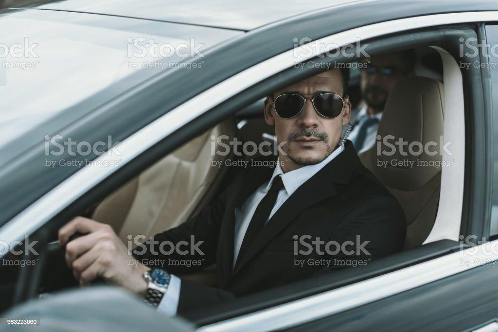 ae80d7fe45 guardaespaldas sentado en el coche con empresario y mirando lejos foto de  stock libre de derechos