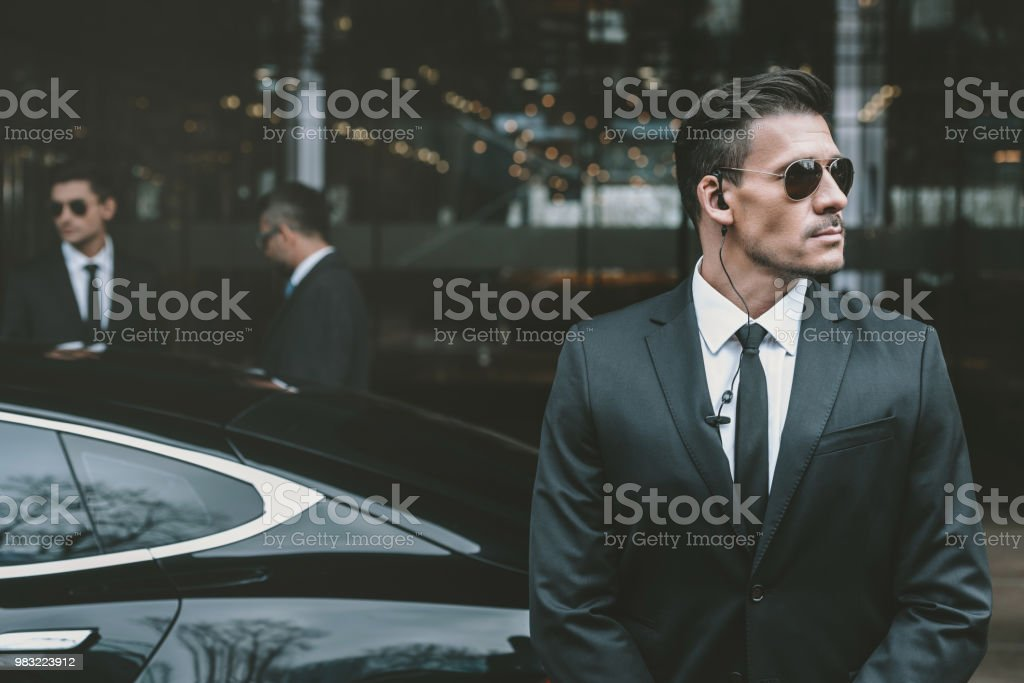 bodyguard standing at businessman car and reviewing territory stock photo