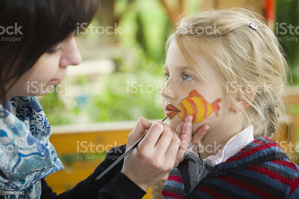 bodypainting - making up fish on girls face royalty-free stock photo