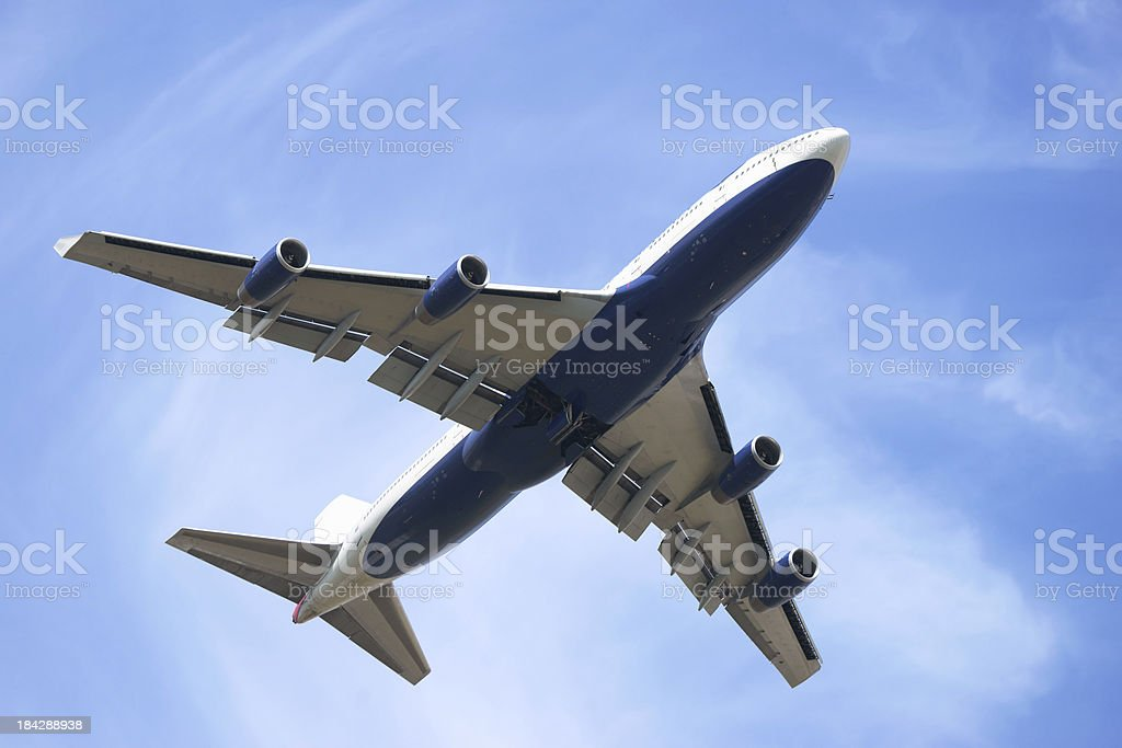 Boeing 747-400 from below against blue sky with light clouds royalty-free stock photo