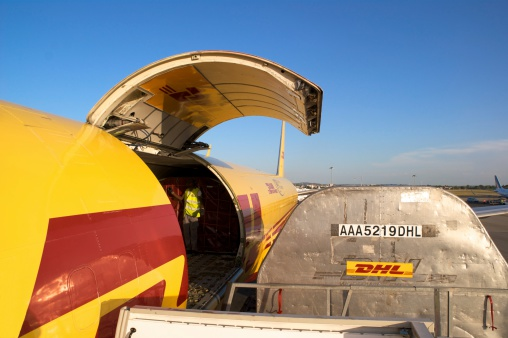 Madrid, Spain - August 14, 2009: A DHL Boeing 757 cargo aircraft loading palletised freight at Madrid airport for onward courier delivery around the world