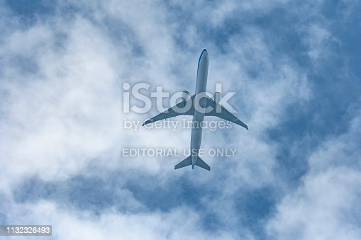 KLM Boeing 777 airplane flying high up in the sky. Upwards view from the ground on the silhouette of the plane with clouds and blue sky in the background.
